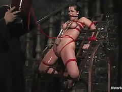 Mia Bangg is bound and gagged in the dungeon where her torturer sprays her nipple-clamped tits. He asks if she wants to get fucked and she does, but first he gives her a little more pain by pulling tight the rope that splits her pussy lips and smacks her cunt before using a dildo on her.