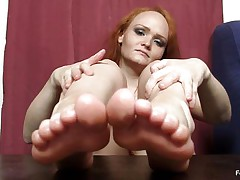 This woman really wants to wrap her feet around a cock and make it cum, but unfortunately that babe does not have a cock handily available. Therefore, that babe is making use of the next best thing, which is a nasty big black fake penis standing up right on the table. She is caressing that with her feet.
