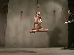 Tied and ball gagged blonde babe Rain is being hanged by her executor. This cunt has a pair of big delicious boobs and a sexy ass with two very tight holes. She's being whipped hard on that ass, spanked on the boobs and then stung on her feet. Look like she will get through a lot so let's enjoy her punishment